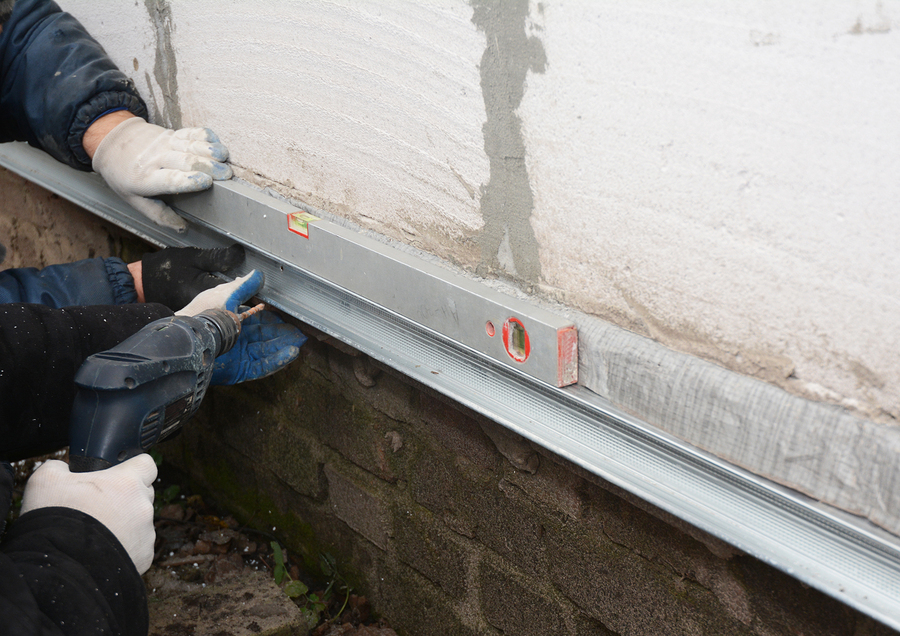 old house foundation wall repair and renovation with installing metal sheets for waterproofing and protect from rain.