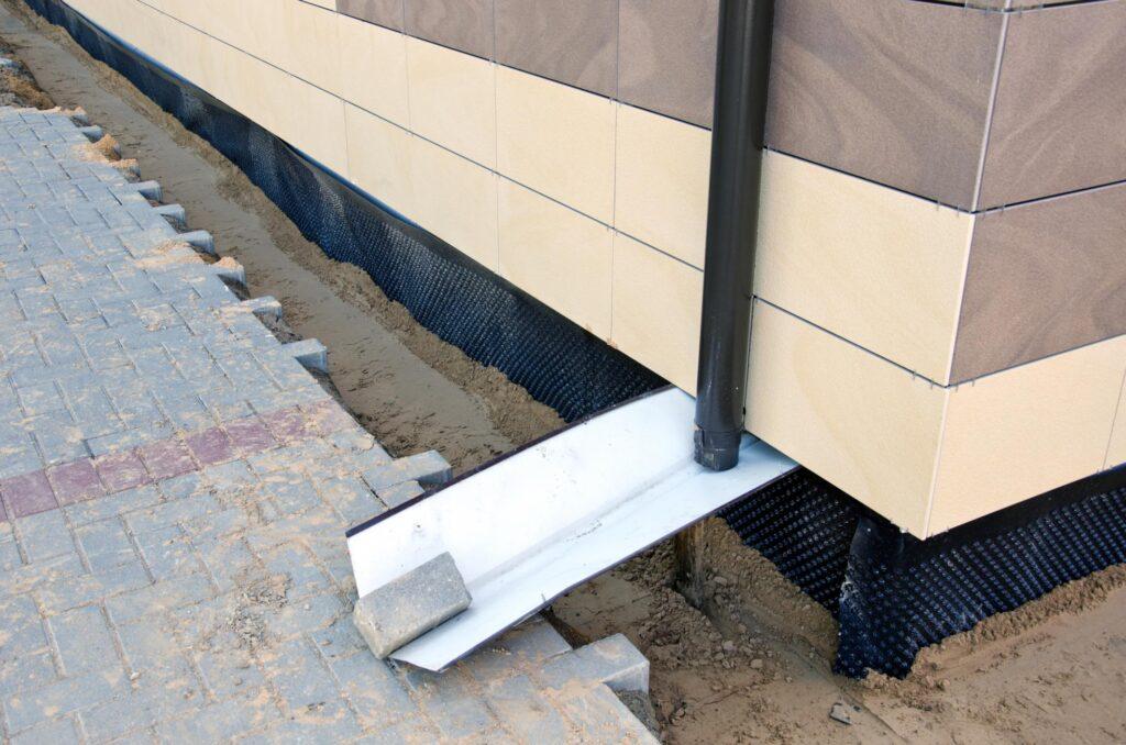 a downward gutter spout with flat tin metal